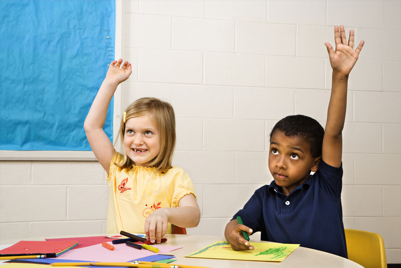 Boy and Girl raising hands in art class. Horizontally framed shot.