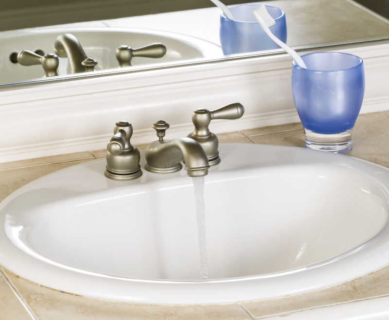 White Bathroom Sink and Faucet in Open Position with Clean Water